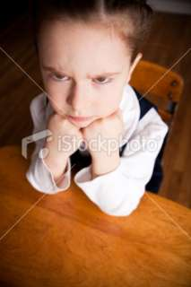 Upset Girl Student Scowling and Sitting in School Desk Royalty Free