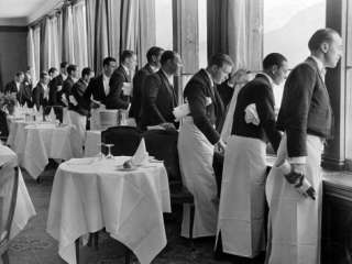 Waiters in the Grand Hotel Dining Room Lined Up at Window Watching